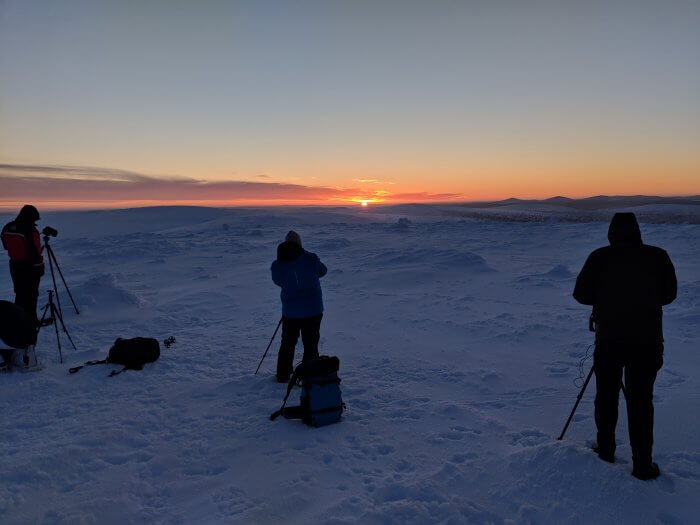 photographers on a field of snow, rising sun in background
